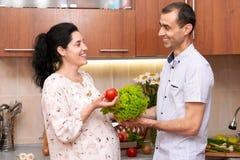 Пары в интерьере кухни с корзиной свежих фруктов и овощей, здоровой концепции еды, беременной женщины и человека Стоковая Фотография