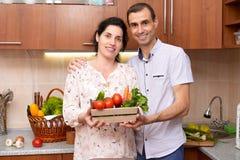 Пары в интерьере кухни с коробкой свежих фруктов и овощей, здоровой концепции еды, беременной женщины и человека Стоковое Фото