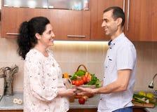 Пары в интерьере кухни с коробкой свежих фруктов и овощей, здоровой концепции еды, беременной женщины и человека Стоковое Изображение RF