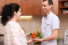Пары в интерьере кухни с коробкой свежих фруктов и овощей, здоровой концепции еды, беременной женщины и человека Стоковое фото RF