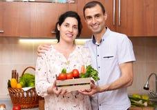 Пары в интерьере кухни с коробкой свежих фруктов и овощей, здоровой концепции еды, беременной женщины и человека Стоковые Изображения