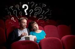 Пары в кино с вопросами стоковая фотография rf