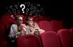 Пары в кино с вопросами стоковые изображения