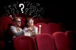 Пары в кино с вопросами стоковое изображение