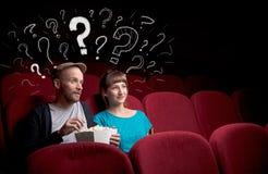Пары в кино с вопросами стоковое изображение rf