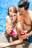 Пары в коктеилях азиатского бассейна гостиницы выпивая Стоковые Фото