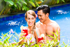Пары в коктеилях азиатского бассейна гостиницы выпивая Стоковое Изображение
