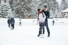 Пары в коньках льда обнимая и смотря один другого Стоковые Фото