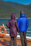 Пары в красочном пурпурном и голубом взгляде Аляске курток скалозуба зимы, coastl США от палубы корабля на солнечный холодный ден стоковые фото