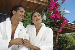 Пары в купальных халатах держа бутылки с водой Стоковое Изображение RF