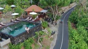 Пары в любов на роскошном курорте на романтичных летних каникулах Люди ослабляя совместно в бассейне края, наслаждаясь видеоматериал