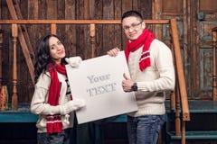 Пары в одеждах зимы держат пустую доску Стоковое Изображение