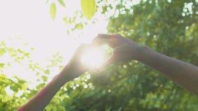 Пары в пальцах переплетения влюбленности в форме сердца пробуя уловить солнце романтичное акции видеоматериалы