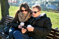 Пары в парке, выпивая кофе и смотреть smartphone Стоковое фото RF