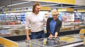Пары в покупках супермаркета с бакалеями магазинной тележкаи покупая видеоматериал