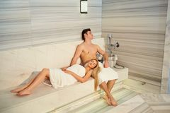 Пары в полотенцах отдыхая в сауне Стоковое фото RF