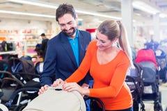 Пары в прогулочной коляске приобретения магазина младенца стоковые изображения rf