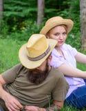 Пары в соломенных шляпах сидят луг ослабляя Выберите правильные одежду и оборудование к походу и пикнику леса Пара стоковые изображения
