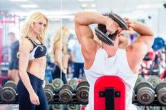 Пары в спортзале фитнеса при гантели поднимая вес Стоковая Фотография