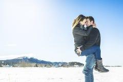 Пары в сцене снега зимы на красивом солнечном дне Стоковые Изображения