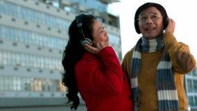 Пары в теплых одеждах наслаждаясь музыкой совместно сток-видео