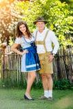 Пары в традиционных баварских одеждах стоя в саде Стоковая Фотография