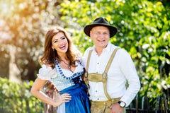Пары в традиционных баварских одеждах стоя в саде Стоковые Фото
