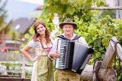 Пары в традиционных баварских одеждах с аккордеоном, зеленым gar Стоковые Фотографии RF