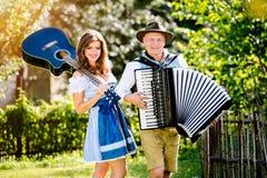 Пары в традиционных баварских одеждах с гитарой и аккордеоном Стоковые Изображения RF