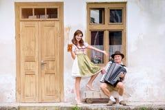 Пары в традиционных баварских одеждах с пивом и аккордеоном Стоковая Фотография