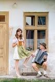 Пары в традиционных баварских одеждах с пивом и аккордеоном Стоковое Фото