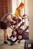 Пары в тренировке спортзала на велосипеде спорта Стоковая Фотография RF