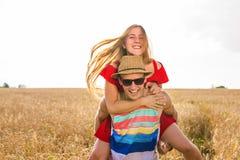 Пары влюбленности имея автожелезнодорожные перевозки в поле лета стоковое фото