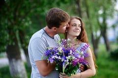 Пары влюбленн в букет обнимают в парке Стоковые Изображения RF
