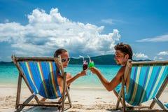 Пары в loungers на пляже на Таиланде Стоковое Изображение