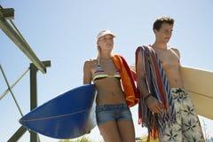 Пары в Surfboards нося Swimwear Стоковое Изображение
