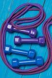 2 пары гантелей и 2 skakaks на голубых досках, покрашенных раковинах спорт, концепции спорта Стоковая Фотография