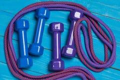 2 пары гантелей и 2 skakaks на голубых досках, покрашенных раковинах спорт, концепции спорта Стоковое Изображение RF