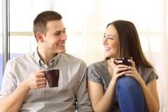 Пары говоря и выпивая дома стоковая фотография