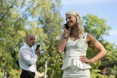Пары говоря на передвижном или умном телефоне Человек и женщина говорят с телефоном Молодые люди мобильного телефона пользы для з Стоковые Изображения RF