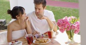 Пары говоря на таблице завтрака снаружи Стоковые Фотографии RF