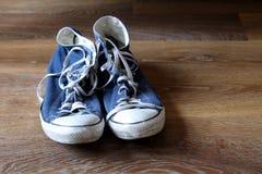 Пары голубых и белых ботинок тренеров тапок на деревянной предпосылке с космосом для текста Стоковые Фото