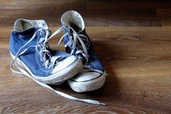 Пары голубых и белых ботинок тренеров тапок на деревянной предпосылке с космосом для текста Стоковые Изображения RF