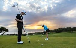 Пары гольфа кладя на зеленый цвет Стоковая Фотография
