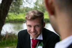 Пары гомосексуалиста grooms представляют для фотоснимок озером на их день свадьбы Стоковые Изображения