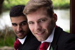 Пары гомосексуалиста grooms представляют для фотоснимок озером на их день свадьбы Стоковое Изображение