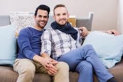 Пары гомосексуалиста держа руки на кресле Стоковое Изображение
