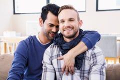 Пары гомосексуалиста обнимая на кресле стоковое фото