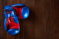 Пары голубых и красных перчаток бокса лежа на коричневом деревянном столе Стоковые Фотографии RF