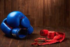 Пары голубых перчаток бокса с 2 кренами повязки руки на деревянной предпосылке Стоковое Изображение